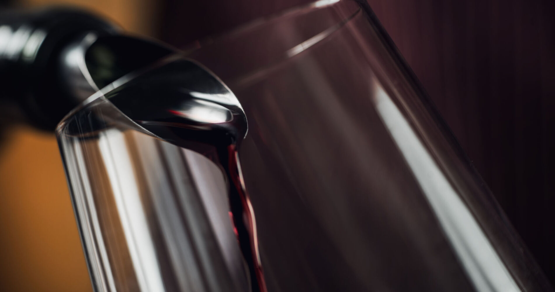 Red wine pouring into wine glass. Bottle with dropstop.